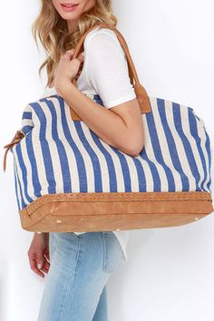 """Need an excuse to splurge? We're saying """"yes please"""" to the I Think I Canvas Blue Striped Weekender Bag! Treat yourself to this extra large, travel-worthy canvas tote with a stylish tan vegan leather flat bottom with protective gold feet, and braided trim. Gold zipper top closure unzips to a spacious striped fabric interior with three side-wall pockets. Carry by tan twin tote handles with 8"""" drop, or attach the shoulder strap measuring 48"""" at longest adjustment."""