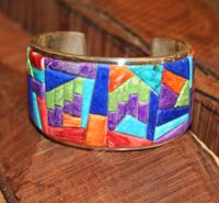Bold Colors Inlay Bracelet  A staff favorite, this unique cuff bracelet is crafted from lapis, coral, turquoise, and orange spiny oyster shell. A bold medley of colors in clean and contemporary silverwork.