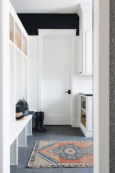 This well appointed home office and mudroom combo features a tan and orange runner place leading to a white built-in bench fixed beneath white open lockers.