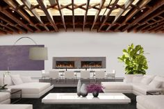 This NYC living room has white sectional couches, an arched floor lamp, glossy coffee table, long dining table, potted plant, exposed rafter ceiling and dual linear fireplaces.