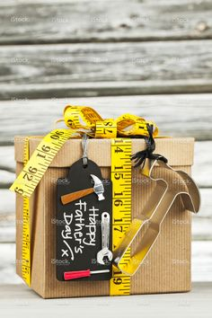Father's Day gift for the DIY dad. Gift decorated with tape measure. Father's Day gift for the DIY dad. Gift decorated with tape measure DIY gift tag and metal hammer shape. Shot against rustic wooden background. Diy Gifts For Dad, Diy Father's Day Gifts, Father's Day Diy, Homemade Gifts, Cute Gifts, Dad Gifts, Grandparent Gifts, Fathers Day Gift Basket, Fathers Day Crafts