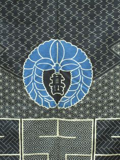 The antique indigo cloth above has a traditional wisteria design with a kanji in the center. It is set against a background of sashiko embroidered traditional patterns. (Tokyo Jinja)