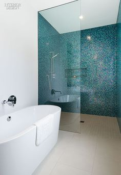 A Toronto home's shower stall from our simply amazing kitchen and bath roundup is clad in a scintillating mosaic of aquamarine glass tile sprinkled with magenta. Photography by Steve Tsai.