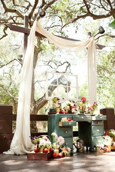 old window and desk used as ceremony decor, tall frame is attached to fence, hanging drapery, hanging old window, old desk, flower baskets, pots, planters everywhere.