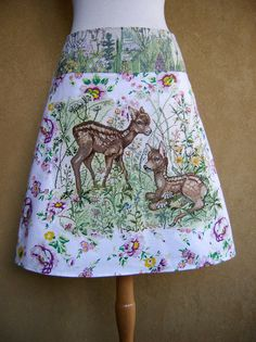 A-line skirt made of cotton. Embellished with a vintage embroidery appliqué. Fully lined. The embroidery is made on white linen and we see two young deer hiding in the grass surrounded by blooming weeds. I recognize clover, dandelion, forget-me-not, thistle, chamomile and cow parsley. The embroidery is extremely well made and the deer are almost alive with white sparks in their beautiful eyes. The embroidery is sewn onto a piece of cotton that was meant to be a tablecloth but was never used…