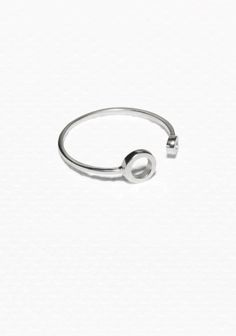 Made from shiny brass, this open ring features two dainty circles in different sizes.