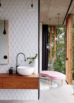 Este banheiro criado pela australiana Jesse Bennett Architect coloca em cheque as noções clássicas de privacidade. A privada e o banho ficam escondidos, mas a pia e a área de vestir são abertas para a natureza, logo ali, através das vidraças. As superfícies surgem com profusão de texturas: concreto, madeira e azulejos tridimencionais, uma tendência forte na decoração. Uma chaise rosa traz conforto. Fica por conta das folhagens impedir que olhares penetrem o espaço. Incrível!
