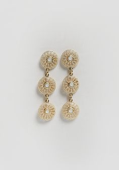 These chic gold-toned earrings are rendered with a hanging design with three circular medallion pendants featuring small textured cutouts and a light blue bead at the center.
