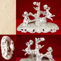 sujets en buiscuit blanc décor anges ailés jouant à la balançoire . XX siècle .