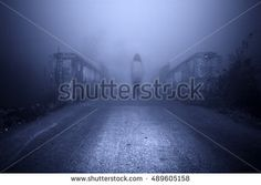 Haunted female ghost at the road in the middle of the misty night.