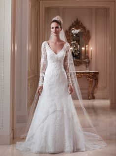 "This gown features a ""V"" front neckline with sheer long sleeves and a demure key hole back. Beaded lace overlay is accented with a beaded appliqué on the center front bodice."
