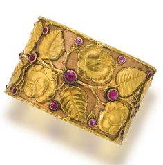 An eighteen karat bicolor gold and ruby bangle bracelet, Buccellati  the cuff designed with a rose and leafy vine motif accentuated by cabochon rubies, signed Buccellati