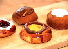 Skønne gammeldags fastelavnsboller, som alle er bagt af samme dej og opskrift. Du kan lave fastelavnsboller som lukkede boller med creme, eller åbne med creme eller hindbærsyltetøj. Pyntes selvfølgelig med glasur. Foto: Madensverden.dk.