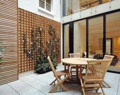 photo of glass wood panel for plant wood panel for plants courtyard garden and chairs table outdoor furniture patio terrace trellis urban garden wall trellis Wall Trellis, Wooden Trellis, Outdoor Furniture, Outdoor Decor, Minimalist Design, Outdoor Gardens, Pergola, New Homes, Outdoor Structures