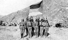Soldiers of the Arab Army in the Arabian Desert carrying the Flag of the Arab Revolt, WW1.