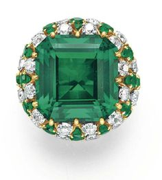A SIMULATED EMERALD RING, BY DAVID WEBB  Set with a square-cut simulated emerald, within a circular-cut diamond and emerald bombé surround, mounted in 18k gold and platinum, circa 1965