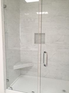 marble tile walk in shower frameless shower door. the tile is Daltile Marissa Cararra, available at Home Depot for $2.21 a square foot.