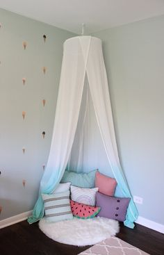 Girls room reading nook with white and teal canopy and pillows