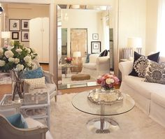 Photo Gallery: Small Spaces | House & Home -- Mirrors and glass are a great trick from creating the illusion of more space in small room.    An oversized mirror adds depth and light to this small yet glamourous living room. A glass-topped coffee table keeps the space feeling airy and bright