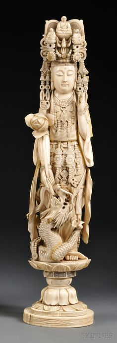 Tall Ivory Carving, China, 19th century, standing figure of Kuan Yin in adorned clothing and headdress, his left hand in the mudra of appeasement position, right hand holding a lotus blossom, a swirling dragon at feet, standing on a lotus base, ht. 18 1/4 in.