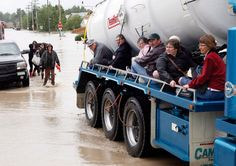 Residents ride on the side of a tanker truck as they are evacuated after heavy rains caused flooding, closed roads, and forced evacuation in High River, Alberta, June 20/13. (THE CANADIAN PRESS/Jeff McIntosh)