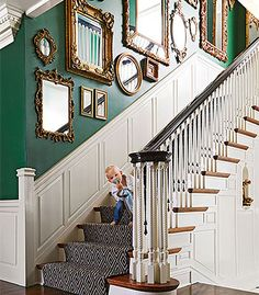 Stylish Update Historic Detroit Home -- I love the wainscotting and the mirrors going up the staircase that bounce the light around!