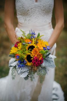 Sunflowers star in this cheery bouquet, which is accented with delphinium, dahlias, solidago, dusty miller and dianthus. Via Little Big Farm and With Love & Embers