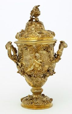 Loving cup with cover by Paul de Lamerie in 1742-43, London. 38.4 ×24.1cm. Victoria & Albert Museum. De Lamerie supplied Lord Mountrath with a similar pair of cups that year (in The Metropolitan Museum). The ambitious decoration is inspired by earlier auricular silver (based on grotesque masks) and the 1720s work of leading Paris goldsmith, Thomas Germain. The skill of this virtuoso craftsman captivates the exuberant vitality of the Rococo style.