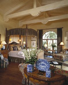 This exquisite master bedroom is enhanced by wood vaulted ceilings, a four-poster canopy bed, and a custom ottoman that houses a television. (I can't imagine ever leaving this room!)