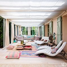 Giorgio Armani's loggia in his Saint-Tropez home with colorful rugs anchoring a blend of current and vintage Armani/Casa furnishings. The vibrant cushions and rugs were found in Saint-Tropez; the two figures with a gong (right) are from Thailand. Saint Tropez, Architectural Digest, Giorgio Armani, Indoor Outdoor Living, Outdoor Rooms, Porches, Interior Decorating, Interior Design, Celebrity Houses