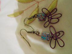 Des boucles d'oreilles fait de billes et d'un motif en fils de fer mauve métallique!