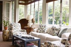 In the sunroom of this Greek Revival home in New Orleans, the sofa features a sturdy cotton duck slipcover that perfectly accents the vibrantly printed chairs.