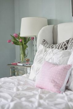 Mirrored bedside table, white bedding and pale pink lumbar pillow