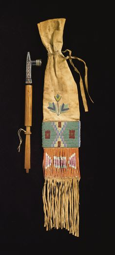 SIOUX PIPE AND BEADED AND QUILLED FRINGED HIDE PIPE BAG    the pipe, of cylindrical and flattend section, decorated at each end with brass tacks, fine aged patina overall, inset to a steatite bowl with catlinite and lead inlay, together with a hide tobacco bag, stitched with opaque and metal beads, with a pair of diamonds on one side, and a butterfly design on the other, surmounted by spot-stitched floral designs; a cut-hide section below wrapped in dyed porcupine quill