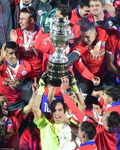 Goalkeeper Claudio Bravo and his team-mates hold the trophy aloft after their penalty shootout win against Argentina
