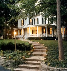 I love the walkway and the porch. Very classic, and the house is set back into the trees. I love that too.
