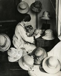 Ladies' hat designer uses oil paint to paint the hats she makes. Each design is different so every hat is a unique product. Kensington, England, 1919