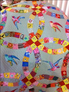 Bright bohemian double wedding ring quilt with sparrow applique from printed fabric all against a grey background. Swoon!