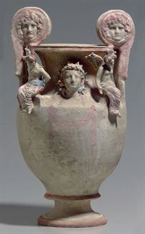 CANOSAN POLYCHROME POTTERY VOLUTE-KRATER  APULIA, CIRCA EARLY 3RD CENTURY B.C.The obverse with a hanging pink fillet, the neck centered by a molded frontal head of Dionysos, wearing an elaborate pink, white & blue fillet of ivy & berries, ties painted along the shoulders, framed by two winged Erotes seated on square platforms along the shoulders, each wearing a pink mantle folded over to blue at the waist, their wings pink, their red hair adorned with pink & blue fillets, volutes with…