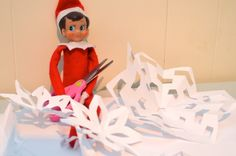 The Elf on the Shelf makes paper snowflakes with scissors