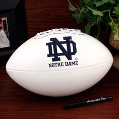 NCAA Notre Dame Fighting Irish Signature Full Size Football by Licensed Products. $29.99. Comes with an autograph pen.. Notre Dame Fighting Irish embroidered team logo displayed on front and school wordmark on back.. 3 smooth white panels for autographs.. This collegiate classic team football features an embroidered team logo prominently displayed on the front and the school wordmark on the back.  An autograph pen is included with each ball and the 3 smooth white panels provid...