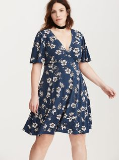 """<div>This dress isn't for the wallflowers. The stretchy navy knit is short (with a mini length) and sweet (with an allover white floral print). But the real attention-grabber is the deeeep v-neck, the bust-boosting seamed front panel, and the relaxed (yet flirty) flutter sleeves.</div><div><br></div><div><b>Model is 5'9.5"""", size 1</b></div><div><ul><li style=""""li..."""