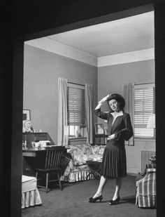 """A woman in a business suit standing in a living room, 1942.  Photo by John Phillips for """"Lonely Wife"""", Dec. 21, 1942.  