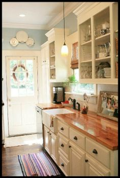 I like the white cabinets with the wood counter-top.  I wonder how well this counter top would hold up?