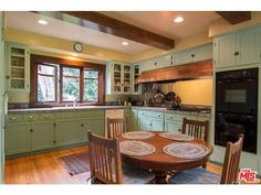1907 Green & Green Arts and Crafts kitchen in Beverly Hills California. Note the copper range hood that extends well beyond the cooktop. This is topped by narrow cabinets with latch closures.