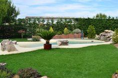 Algunas plantas y rocas dan a esta piscina de arena un aspecto completamente natural y la ayudan a integrarse en el entorno. Esta piscina está realizada con NaturSand, nuestro sistema exclusivo y patentado de arena natural compactada. #piscina #arena #arenanatural #NaturSand #paisajismo #jardín #Piasajismojardines