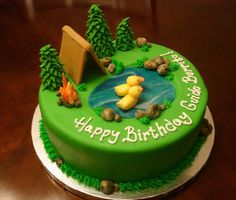 Green round camping theme cake with pond and ducks and tent.JPG