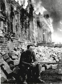 Defeated German soldier in front of burning Reichstag. Berlin, 1945