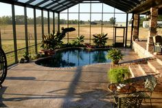 A greenhouse, attached to the house with one wall that can open up, with a heated pool and hot tub inside, bar area with big screen, stereo surround