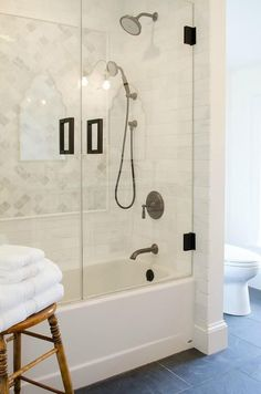 A white and gray themed bathroom with marble arabesque tiles on the shower walls, and black slate tile underfoot, create a fresh and inviting bathroom.